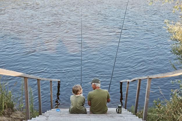 Senior man vissen met kleinzoon, tijd doorbrengen in de buurt van rivier