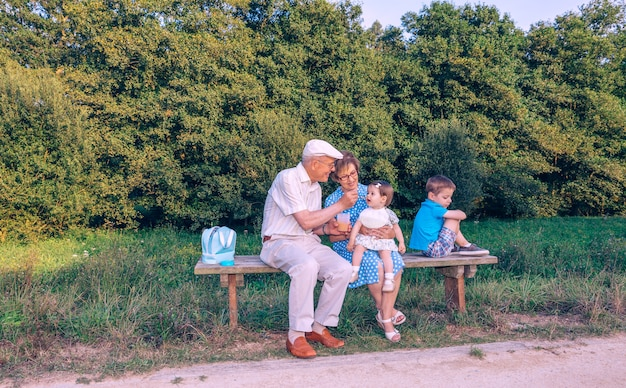 Senior man voedt met fruitpuree aan schattig babymeisje terwijl een jaloerse broer zijn rug toekeert terwijl hij buiten op een bank zit. grootouders en kleinkinderen relaties concept.