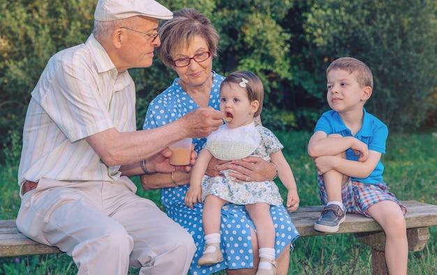 Senior man voedt met fruitpuree aan schattig babymeisje zittend over een senior vrouw in een bankje buiten. grootouders en kleinkinderen levensstijl concept.