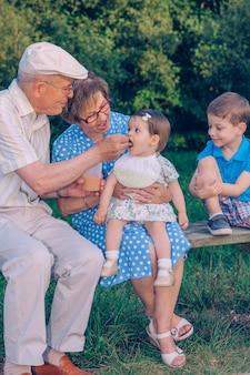 Senior man voedt zich met fruitpuree aan een schattig babymeisje dat over een senior vrouw in een bankje buiten zit. grootouders en kleinkinderen levensstijl concept.