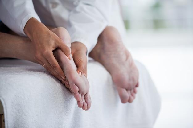 Senior man voetmassage ontvangen van fysiotherapeut