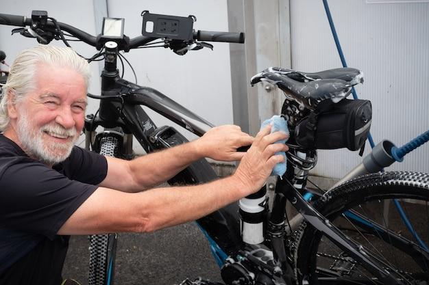 Senior man wast zijn fiets en zorgt voor de details tankstation hogedrukpomp