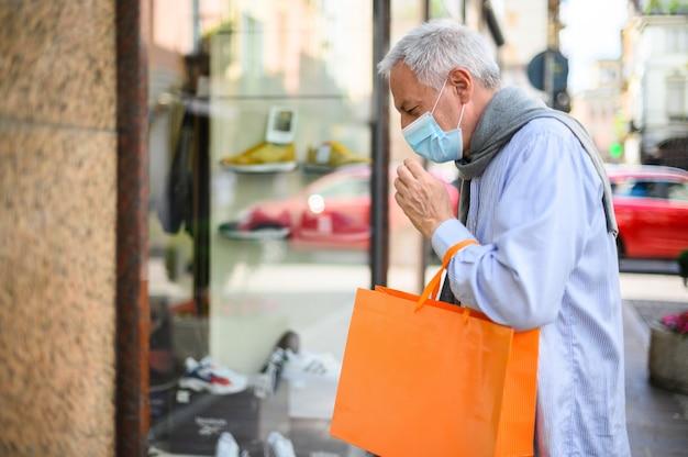 Senior man winkelen buiten met een masker tijdens coronavirus tijden
