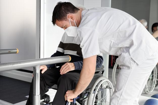 Senior man wordt bijgestaan door fysiotherapeut in rehab center.