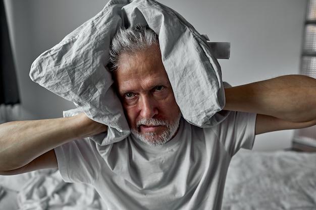 Senior man wordt gek van slapeloosheid, bedekt zijn oren met een kussen, band en uitgeput