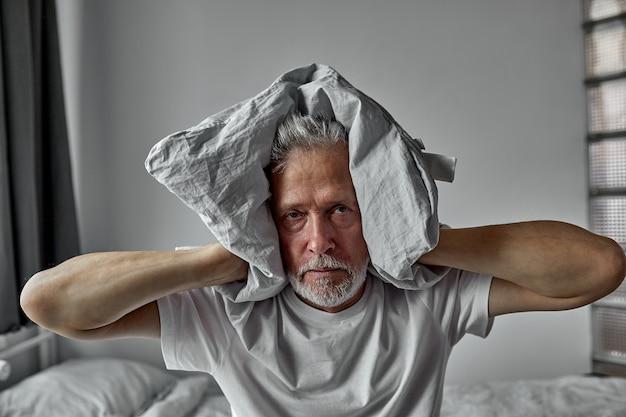 Senior man wordt gek van slapeloosheid, bedekt zijn oren met een kussen, moe en uitgeput