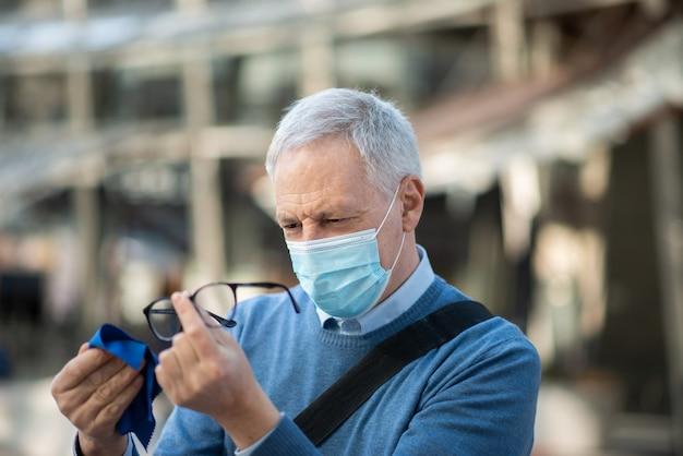 Senior man zijn bril schoongemaakt beslagen vanwege het masker, covid coronavirus visie concept
