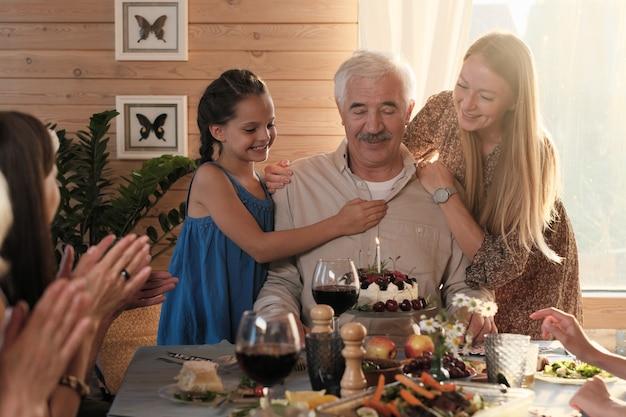 Senior man zit aan de tafel met verjaardagstaart terwijl zijn kleindochters hem feliciteren met verjaardag thuis