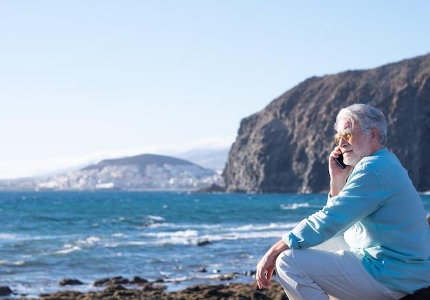 Senior man zit bij zonsondergang op het strand met behulp van mobiele telefoon, kijkend naar de horizon over water