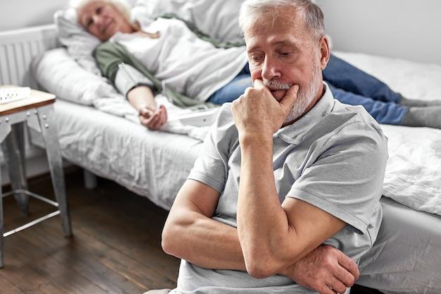 Senior man zit met haar zieke zieke vrouw liggend op bed, voelt zich slecht, vrouw staat voor de deur, man maakt zich grote zorgen om haar