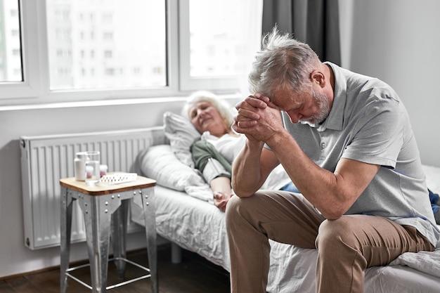 Senior man zit met haar zieke zieke vrouw liggend op bed, zich slecht voelen, vrouw staat voor de deur van de dood, man maakt zich grote zorgen om haar