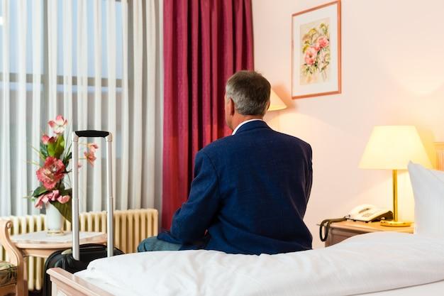 Senior man zit op het bed in de hotelkamer