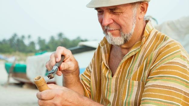Senior man zit op het strand en fluit maken door handen, close-up.