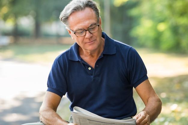 Senior man zit op park krant lezen