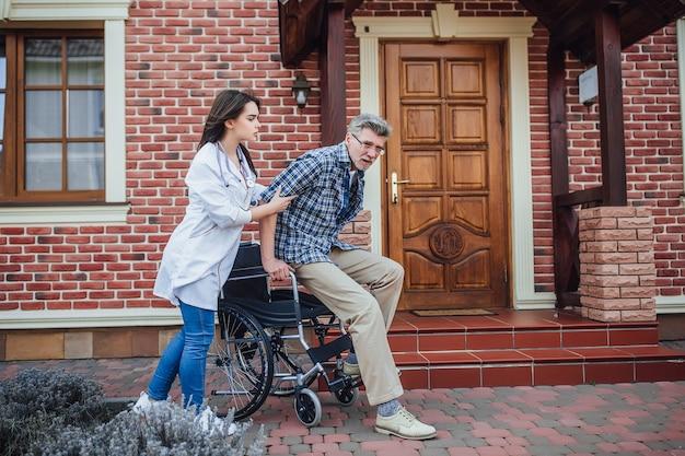 Senior man zit op rolstoel met lachende verpleegster, zorgt en discussieert en juicht in de tuin van verpleeghuis