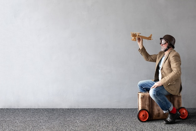 Senior man zit op vintage koffer. volledig lengteportret van grappige mens tegen betonnen muur met exemplaarruimte