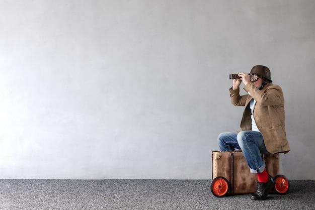 Senior man zit op vintage koffer. volledig lengteportret van grappige zakenman tegen concrete muur met exemplaarruimte. opstarten bedrijfsconcept