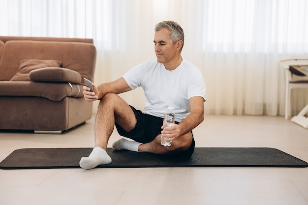 Senior man zit op yogamat en sms't op smartphone