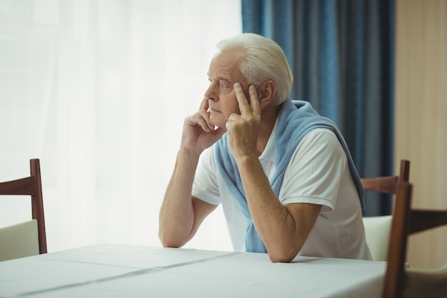 Senior man zittend aan een tafel