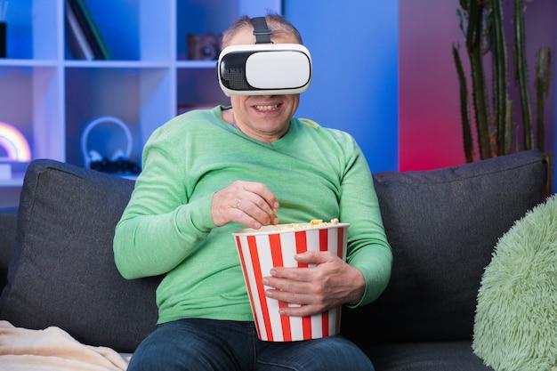 Senior man zittend op de bank en met popcorn, hij draagt een virtual reality-bril en heft zijn hand op om selectief te zijn met vr-scherm.