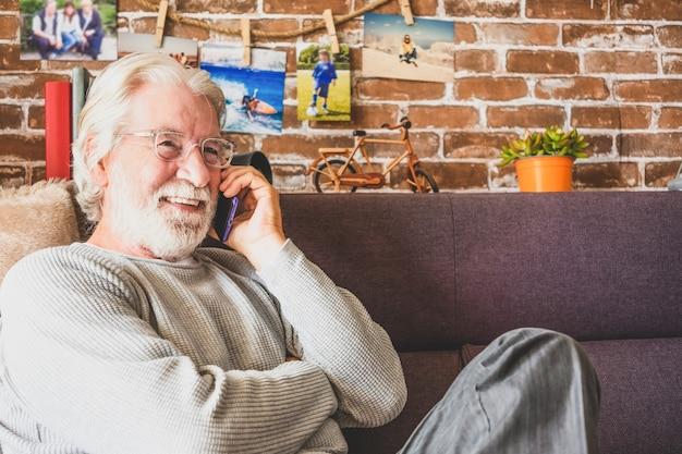 Senior man zittend op de bank thuis praten met mobiele telefoon. gepensioneerd vrijetijdsmensen concept