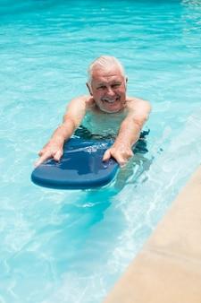 Senior man zwemmen in het zwembad op een zonnige dag