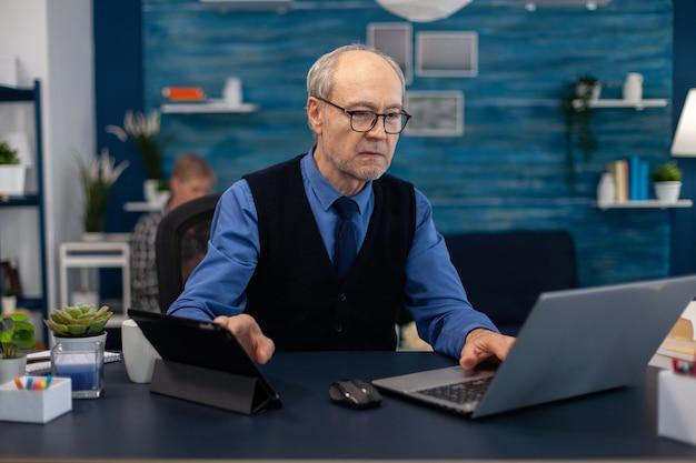 Senior manager bezig met presentatie met behulp van laptop en tablet pc zittend op kantoor oudere man ingang...