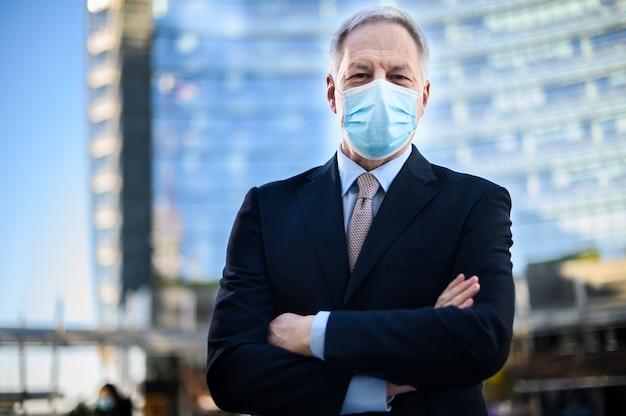 Senior manager met gevouwen armen die buiten een beschermend masker draagt tegen covid 19