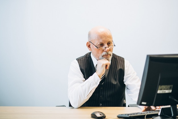 Senior manager op kantoor werkt op een computer