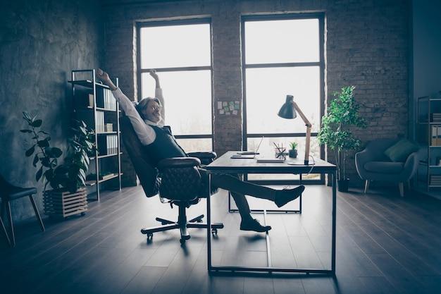 Senior manager zit stoel handen uitrekken op kantoor