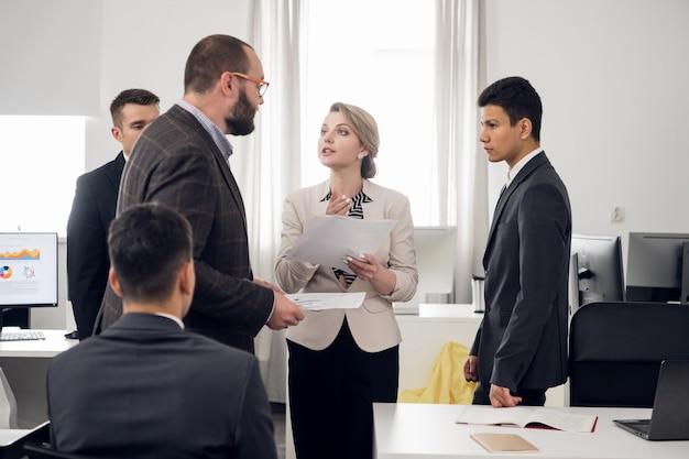 Senior managers en stagiaires houden een bijeenkomst in het witte kantoor van het hr-bedrijf. open ruimte zone. meerdere mensen