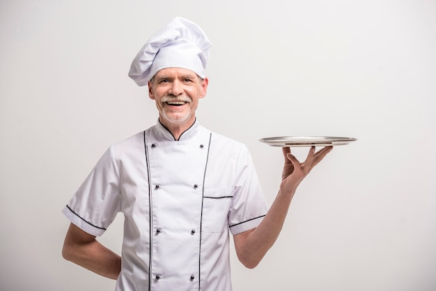 Senior mannelijke chef-kok in uniform dienblad.