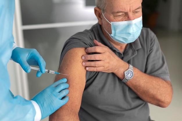 Senior mannelijke patiënt die wordt gevaccineerd tegen coronavirus