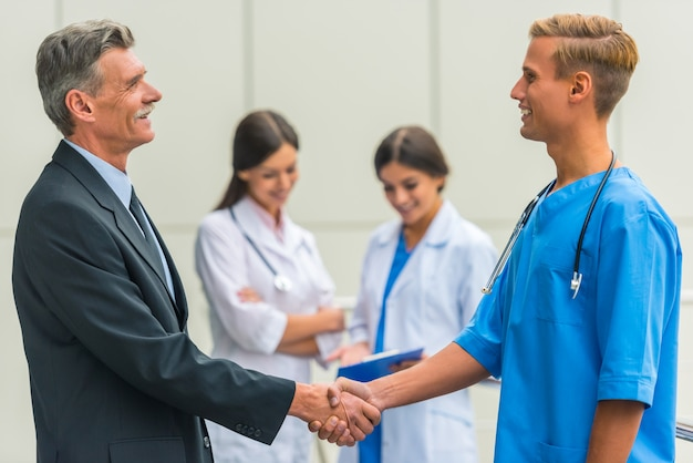 Senior mannelijke zakenman schudt handen artsen in het ziekenhuis.