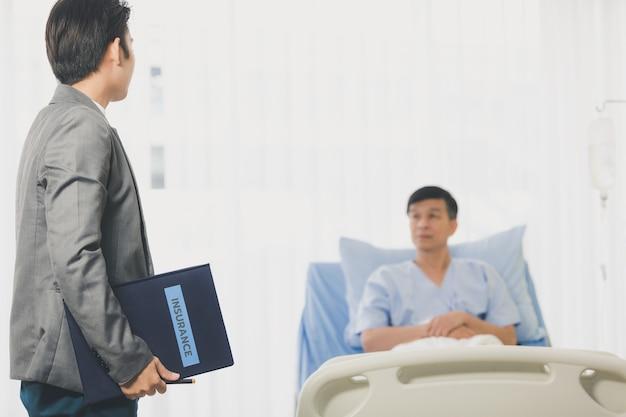 Senior mannen liggend op het bed tijdens de ziekenhuisvergadering met financieel adviseur, senior vrouw die contract leest. beiden droegen hygiënemaskers om uitbraken van ziekten te voorkomen.