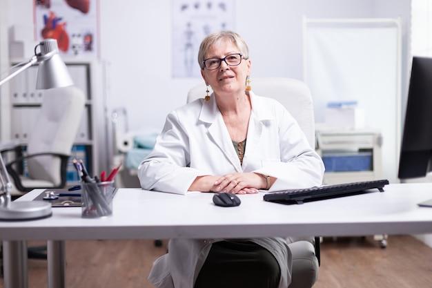 Senior medic glimlacht tijdens videovergadering met patiënten die aan de balie in de medische kliniek zitten. pov van een arts die online spreekt in de ziekenhuiskamer en naar een camera kijkt die een laboratoriumjas draagt tijdens telegeneeskunde
