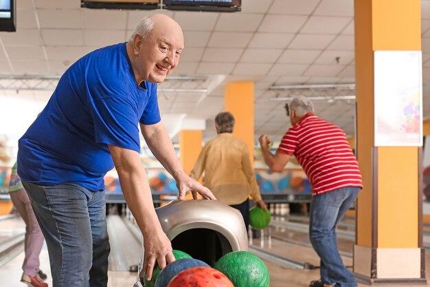Senior mensen spelen bowling in club