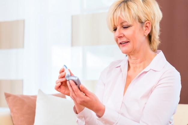 Senior met diabetes met behulp van bloedglucose-analyseapparaat