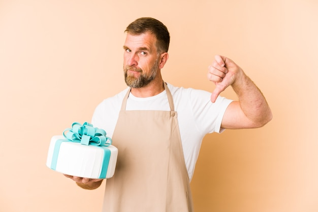 Senior met een cake geïsoleerd op een beige achtergrond met een afkeer gebaar, duimen naar beneden. meningsverschil concept.