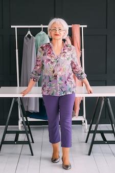 Senior modestylist. succesvolle zakendame. lachende oudere vrouw poseren in stijlvolle showroom.