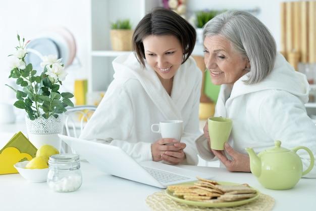 Senior moeder en volwassen dochter met laptop en thee samen
