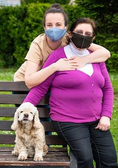Senior moeder met dochter in medische gezichtsmaskers ontspannen in het park
