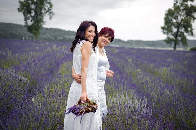Senior moeder met volwassen dochter die op het lavendelveld loopt