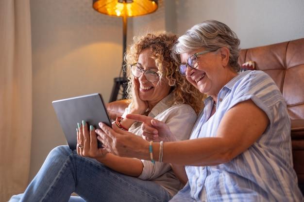 Senior moeder met volwassen mooie dochter thuis glimlachend samen op zoek naar iets grappigs op digitaal apparaat