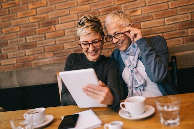Senior moeder zit in café-bar of restaurant met haar dochter van middelbare leeftijd en geniet van een gesprek.