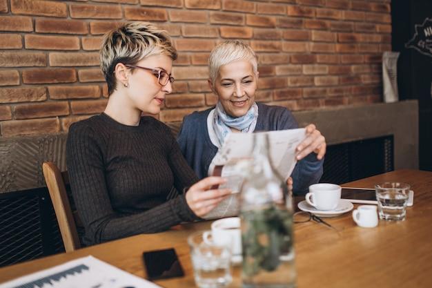 Senior moeder zit in café-bar of restaurant met haar dochter van middelbare leeftijd, ze lezen kranten en genieten van een gesprek.
