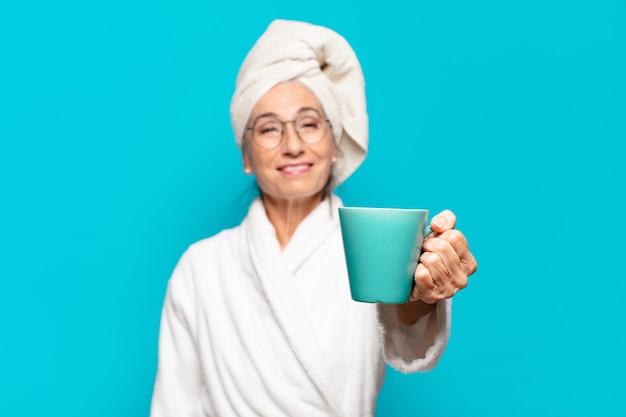 Senior mooie vrouw badjas dragen en met een kopje koffie