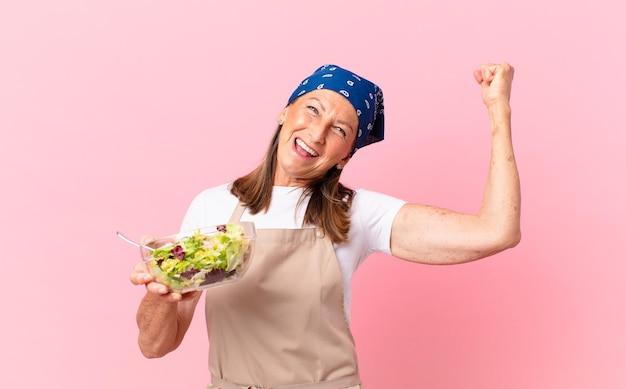Senior mooie vrouw die een salade bereidt