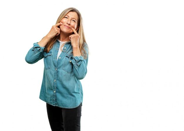 Senior mooie vrouw dwingen een glimlach op het gezicht met beide wijsvingers, alsof het verzenden van een