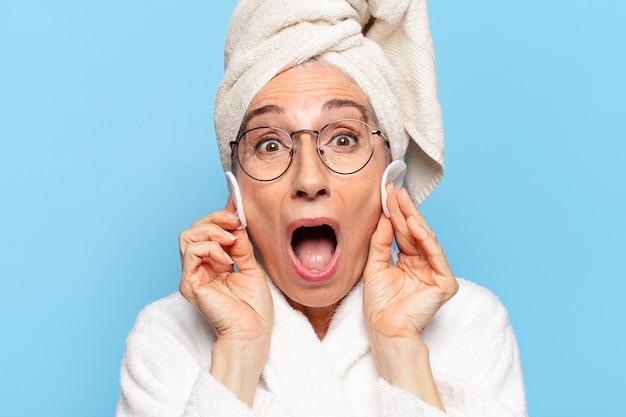 Senior mooie vrouw gezichtsreiniging of make-up na douche badjas dragen
